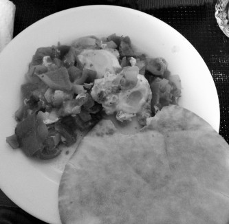 Eating the shakshouka with pita. Photo in black and white.