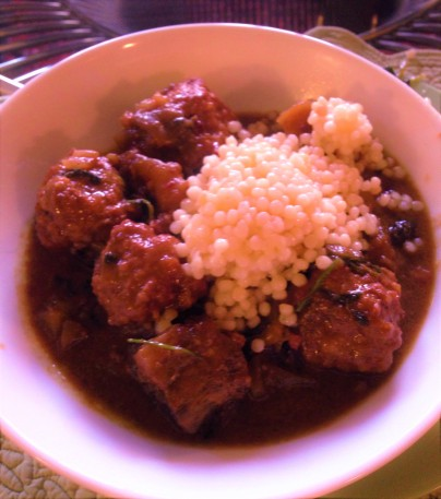 Stewed meatballs with eggplant and fruit, served with maftoul.