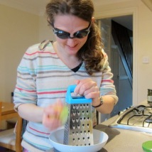 Dalya grating onions into a bowl while wearing goggles