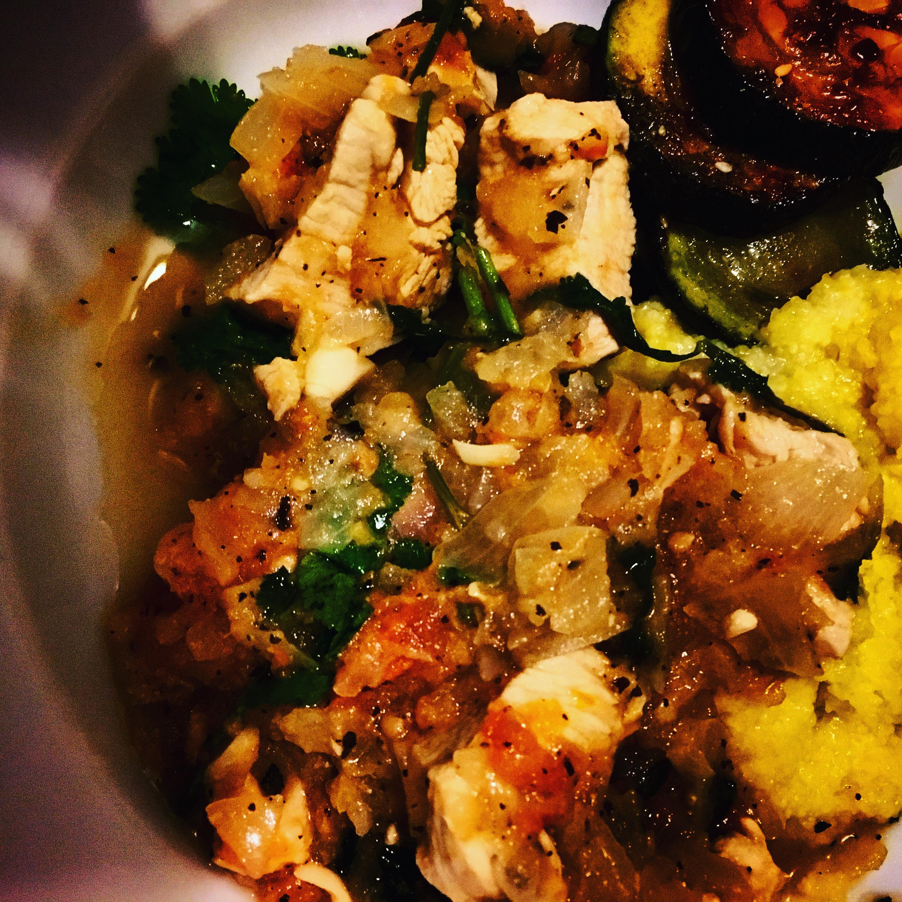 Chicken stew with tomato, cilantro, and onion, with cornmeal porridge and zucchini medallions