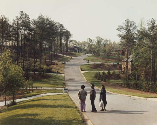 Three black women standing on a road in a suburban setting