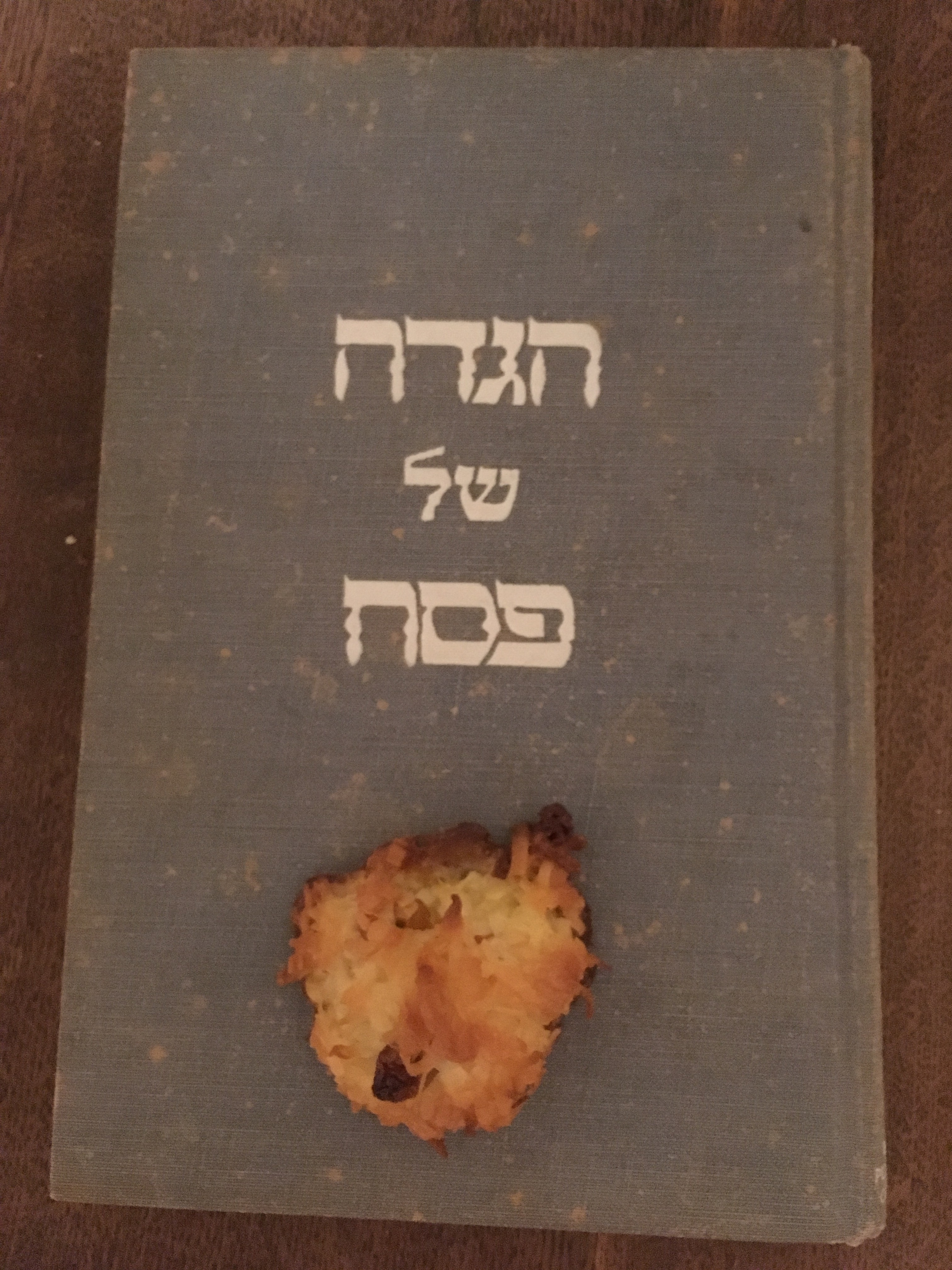 A macaroon sitting under the title on the cover of a haggadah for Passover