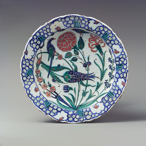 A floral plate from Iznik with a bird and flowers and plants, blue pattern on the rim.