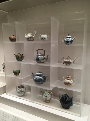 12 porcelain teapots, some from China and Japan and some European imitations, in a glass case. Several are blue and have floral patterns.