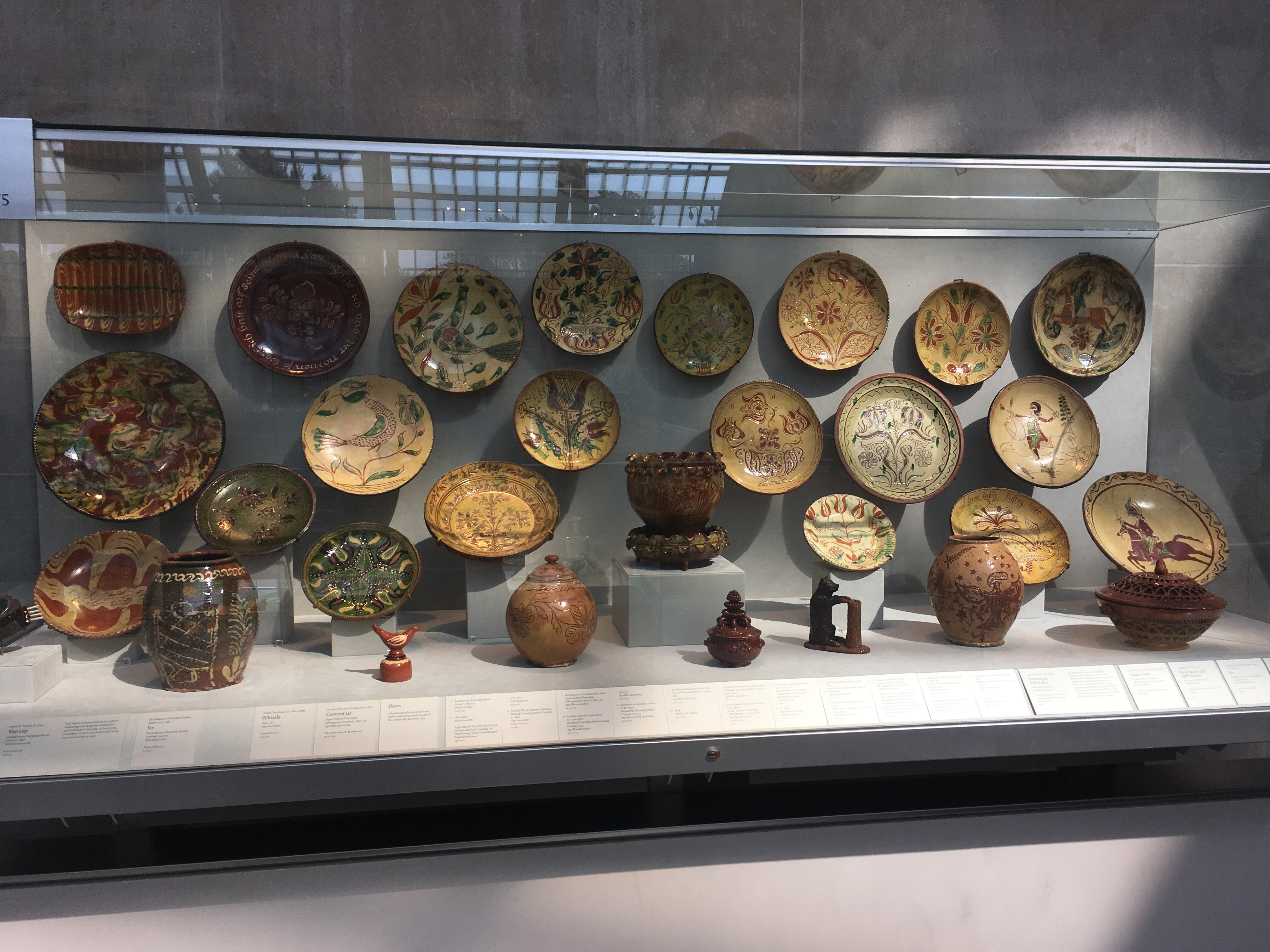 A large case with about 20 pieces of Pennsylvania redware dishware