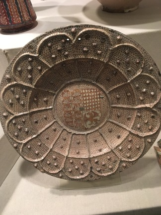 An inlaid plate from Spain with a copper luster and a family shield in the center.