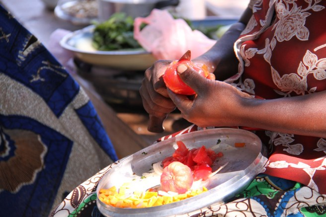 A black woman peeling a tomato over a plate with a peeled tomato, peels, and chopped pumpkin, with greens in the background.