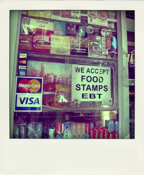 "A deli window with a sign that says ""we accept food stamps EBT"" with Doritos and Lays bags behind it, and toothpaste below."