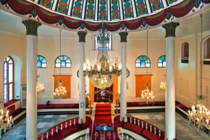 The Mayor Sinagogu in the city of Bursa. There is a painted dome in blue, green, and red, with white columns with green heads above the bima, which is red. There is a chandelier in the middle and white walls with blue glass windows.