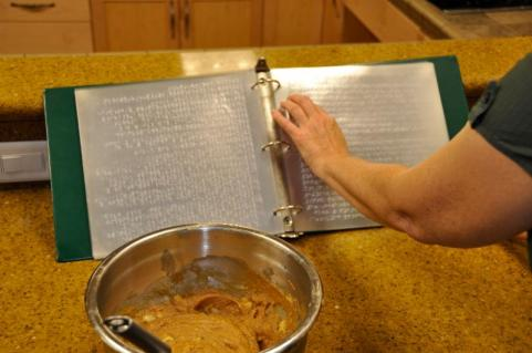 A white hand moving over a braille cookbook in a green binder. A bowl with a brown batter and a whisk is in the foreground.