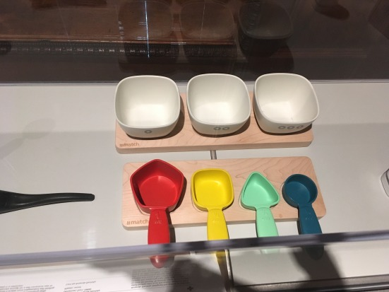 Colored scoops of different shapes and colors on a wooden board with three bowls behind it, each bowl has a number of circles.