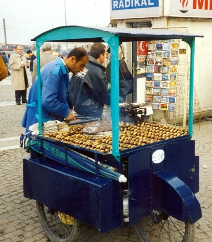 A kestaneci, or roasted chestnut vendor, in Istanbul. He is wearing a blue jacket with roasted chestnuts and a roasting pan on a blue cart.