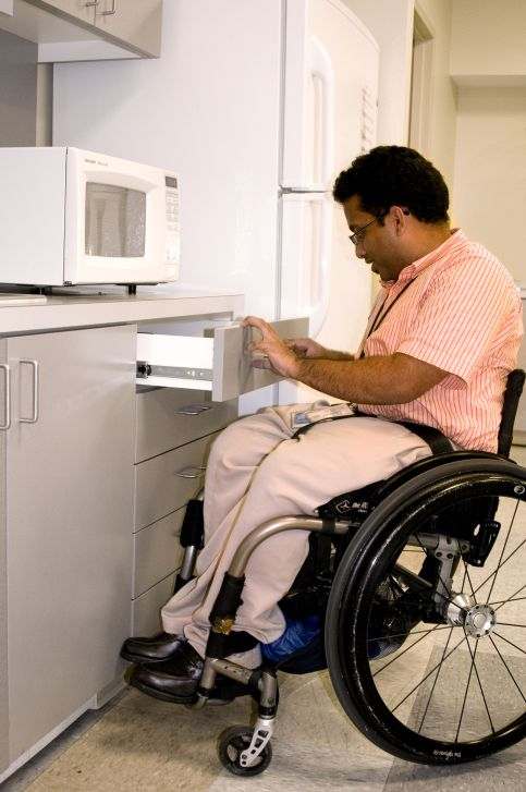 A man using a wheelchair opening a drawer under a microwave in front of a fridge.