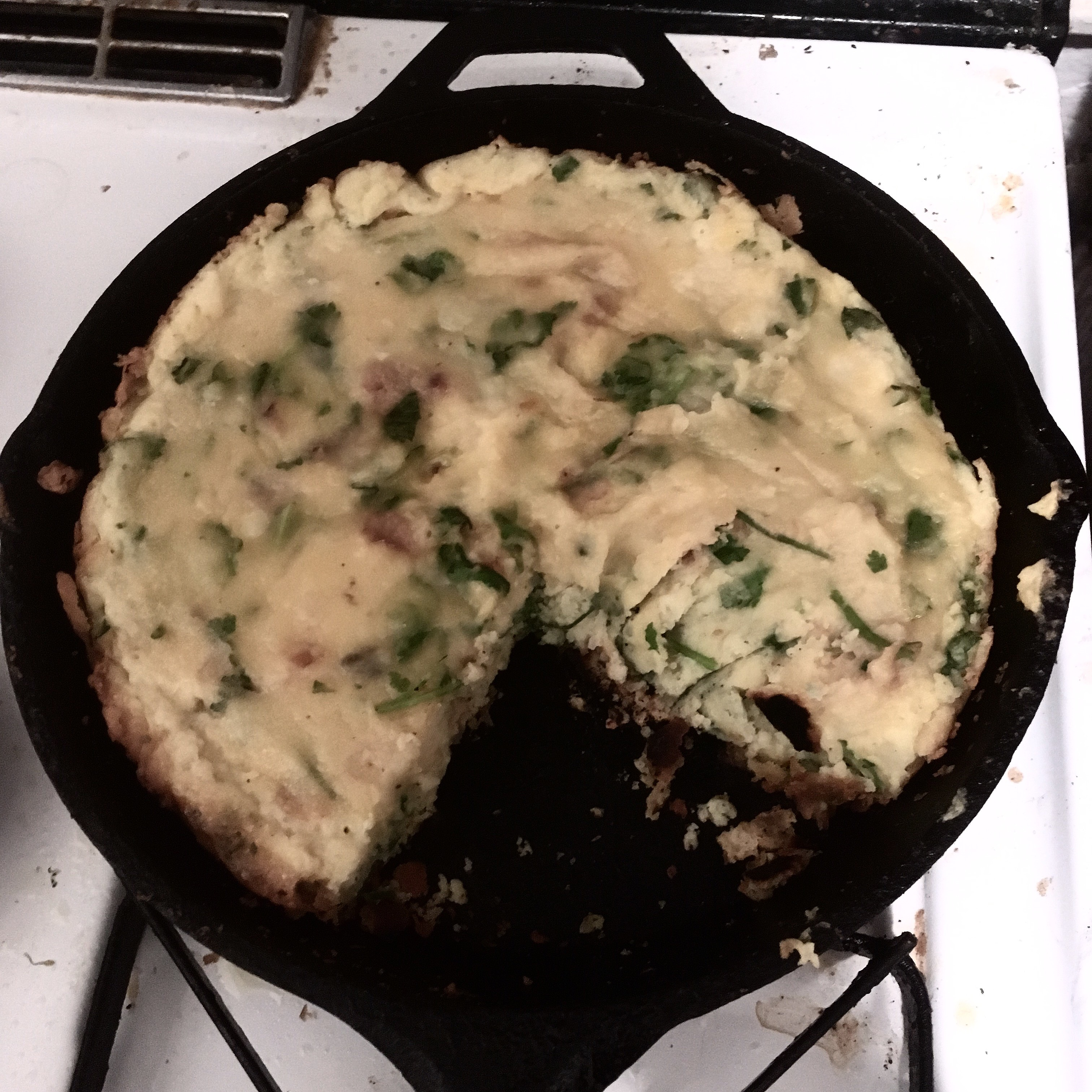 Potato frittata with cilantro and chilies in a cast-iron pan with a missing section cut out