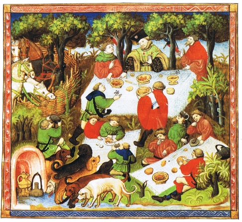 Medieval illumination of noblemen in traditional tunics and boots around tables eating meats and breads under trees and drinking. Dogs are drinking at a creek in the foreground. The trees are tall and in full foliage, the image has red and blue illuminated borders.