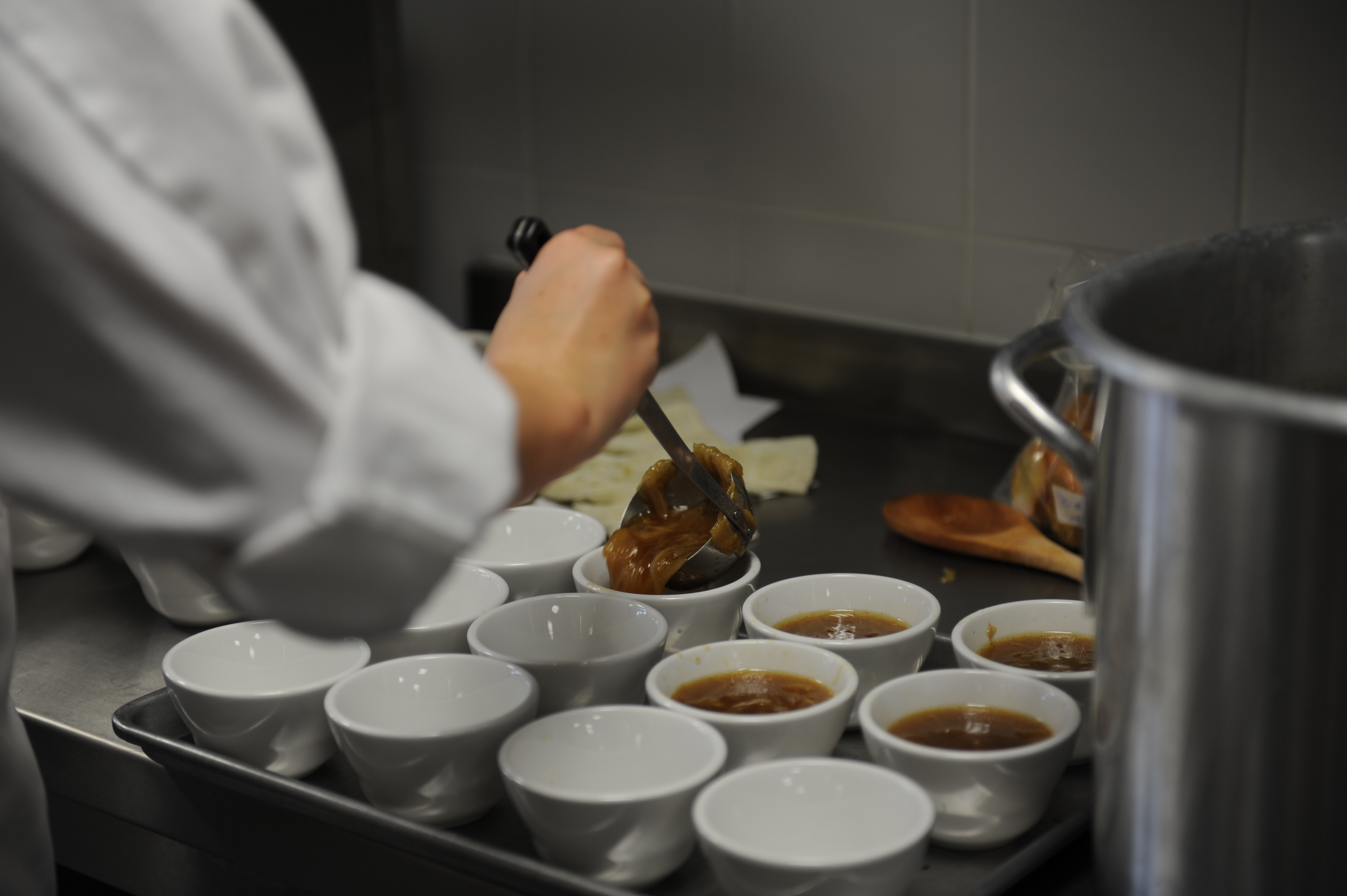 A cook ladles brown onion soup into bowls, four of which are full and eight of which are empty. A large pot is to her side.
