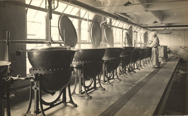 Several giant metal pots stand over braziers, with a man in a chef's uniform stirring one. The pots are steaming. Photo is black and white.