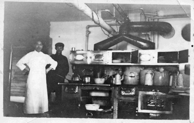 Two Indigenous men in smocks stand by a shelf and stove with pots in a black-and-white photo