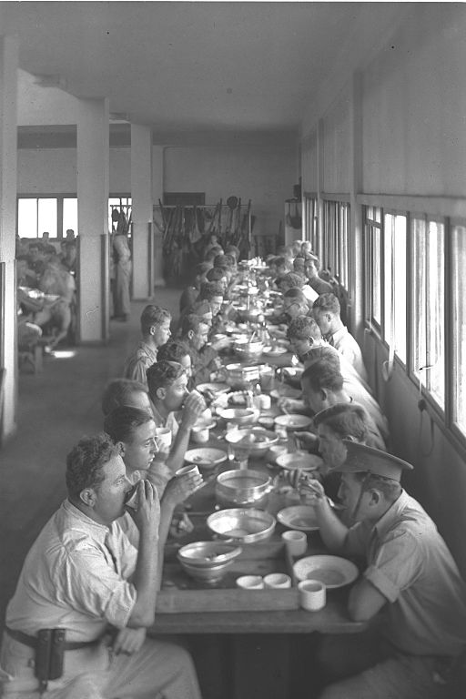 Men at a long table eating a communal meal