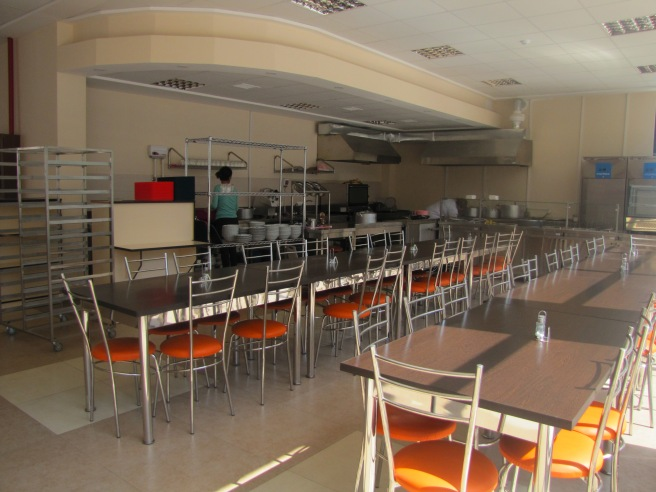 Long tables with chairs with orange seats arrayed in a cafeteria with a food service area with a stove and stacked bowls behind it. Rolling trays are on the left.