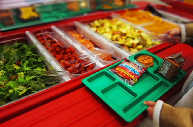 School lunch tray with snacks and chocolate milk and tray of vegetables