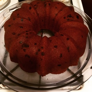 Round Bundt chocolate cherry cake on a glass tray