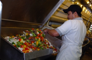 A food service worker preparing a stir fry in a large community kitchen