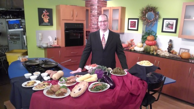 Rabbi Jason Miller, a tall whie man, stands behind a table with food in a kitchen.