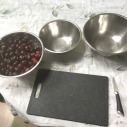 Cherries in a bowl with a knife and board