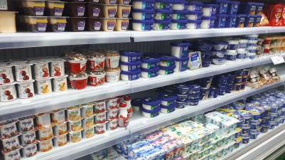 A refrigerator with four shelves stacked with packaged dairy products