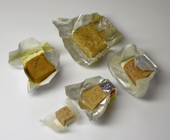 Five brown bouillon cubes in open wrappers.