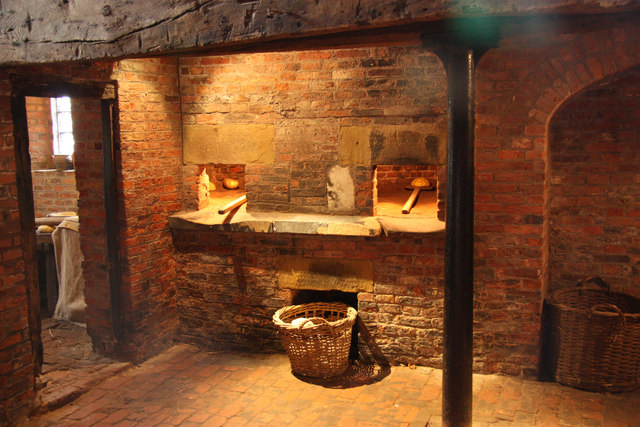 A medieval oven with two wooden sticks going into holes in a brick edifice, with a fire within