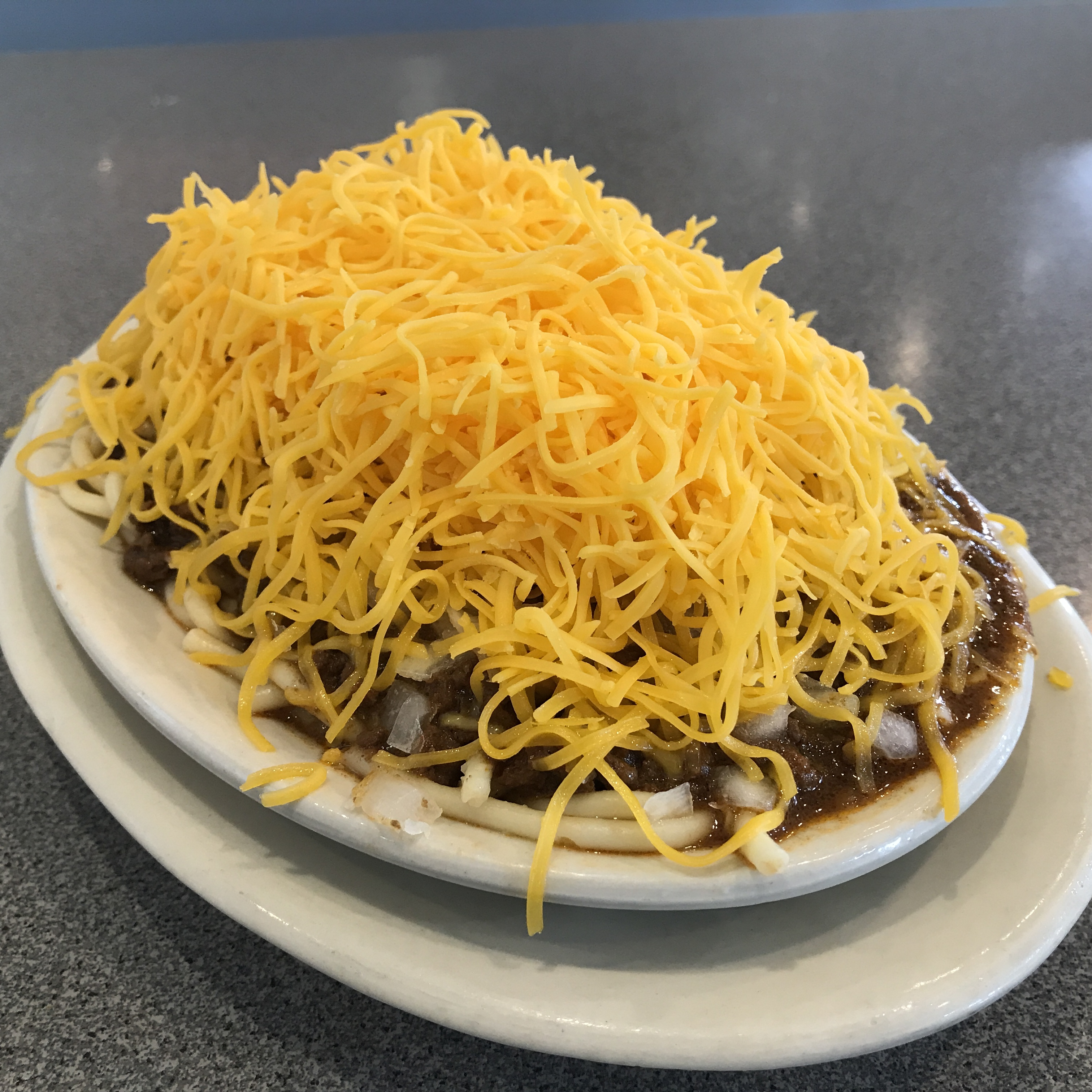 Bowl of meaty Cincinnati chili with cheddar cheese on top.