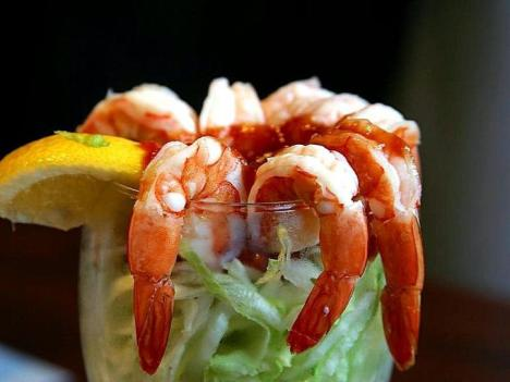 A shrimp cocktail with a lemon over lettuce