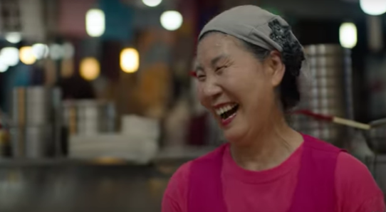 A laughing Korean woman with a gray headband and a pink smock with pots in the background