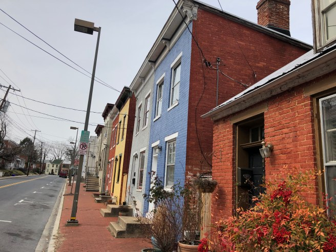 A narrow brick sidewalk by colorful brick rowhouses with poles and stairs in the way