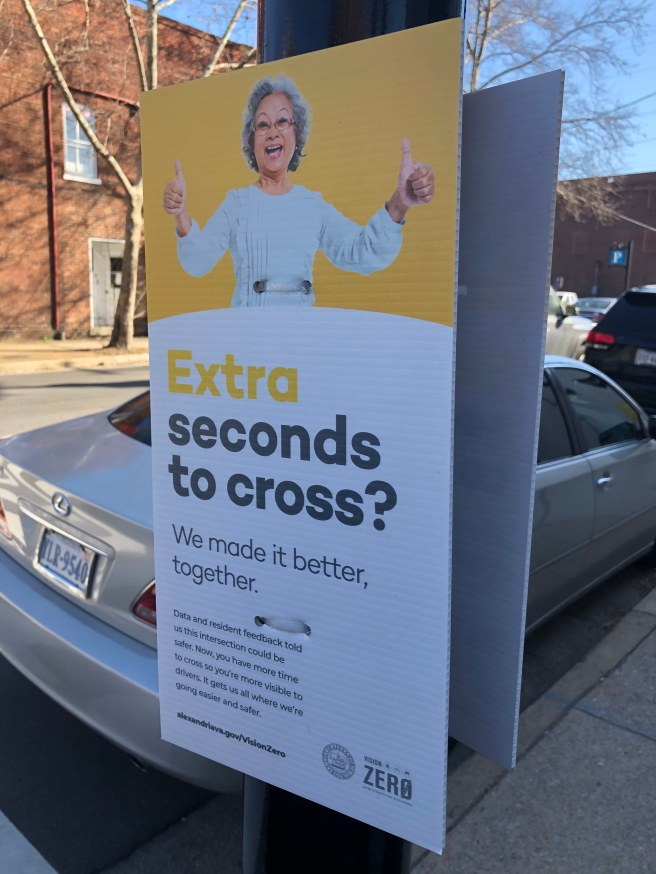 "A sign with an Asian elder woman with thumbs up on a street pole, saying ""Extra seconds to cross? We made it better together."