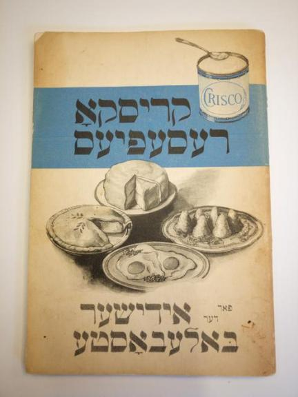 "Yiddish-book with food images on cover, reading ""Krisko resepies far der idisher baleboste/Crisco recipes for the Jewish housewife"""