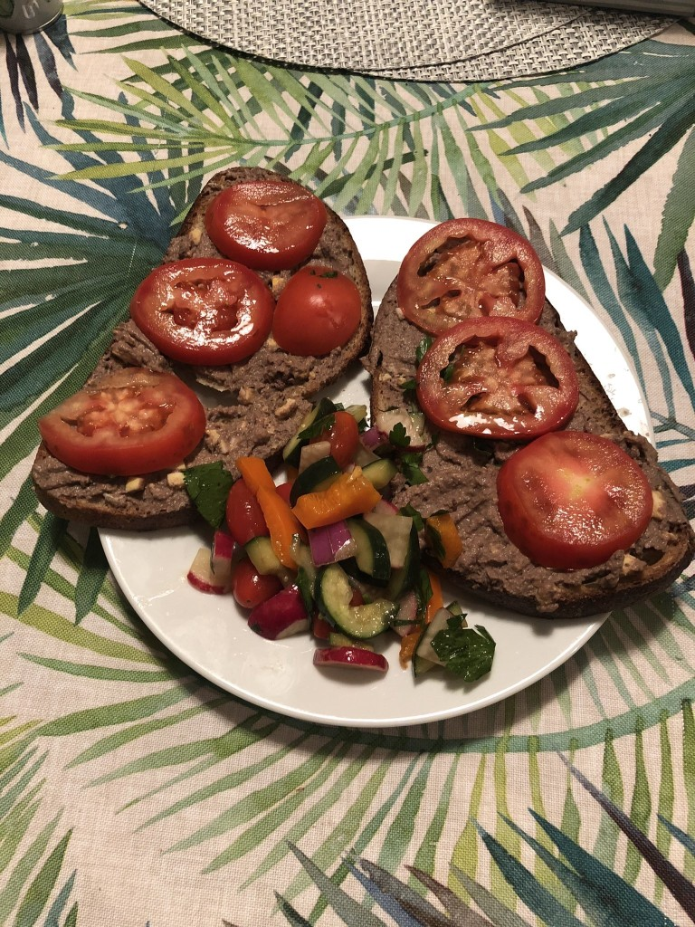Chopped liver on bread with tomatoes with salad on a plate on a floral tablecloth
