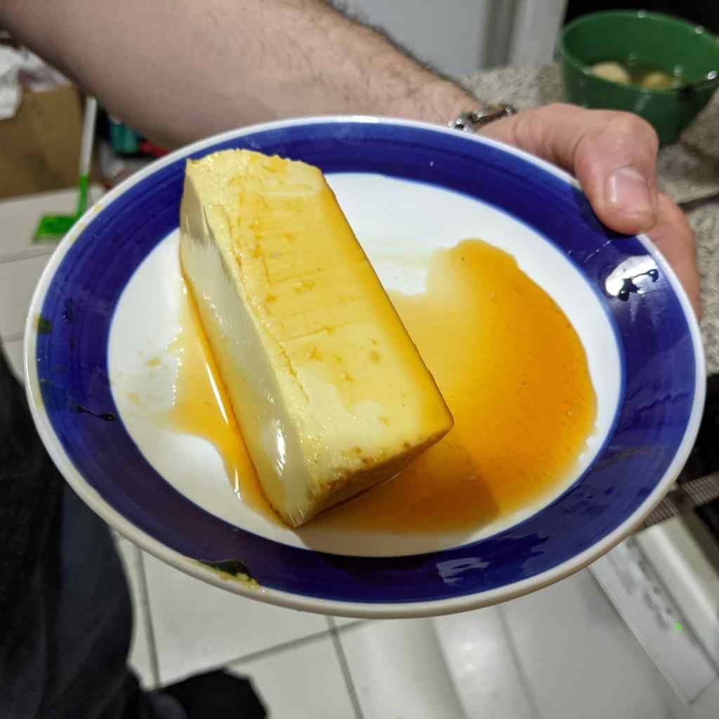 A slice of flan on a blue and white plate